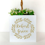 Metal plant pot personalised with names in gold letters for a wedding.