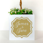Metal planter with names in white in a gold frame.