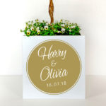 Personalised metal plant pot with first names in white on a gold background.