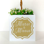 Plant container for wedding arch in gold and white.